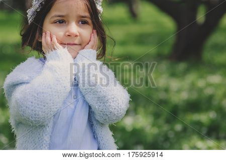 adorable toddler child girl in light blue dressy outfit walking and playing in blooming spring cherry garden