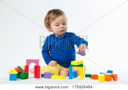 Little child playing with dices isolated on white background.