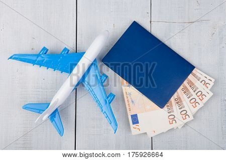 Plane, Passport And Paper Money On White Wooden Table