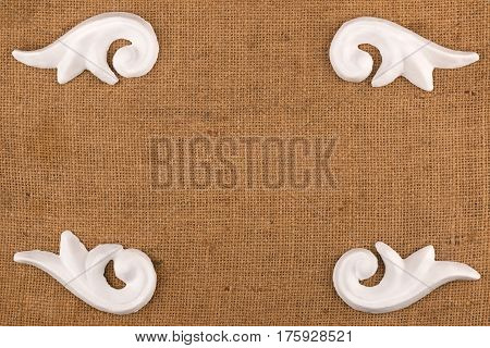Luxury frame made of white stucco plaster lying on burlap. With space for your text