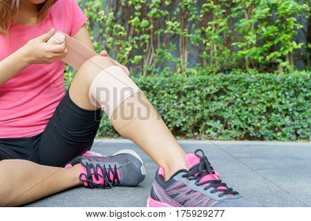 Young woman runner knee being applied bandage by herself in park. injury joint concept