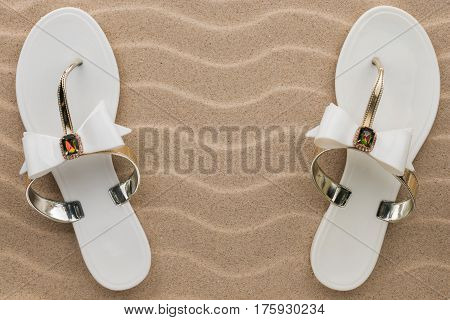 Pair of white beach sandals in rhinestones stand on the sand. View from above