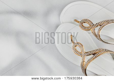 Pair beach white sandals in rhinestones standing on white silk. View from above