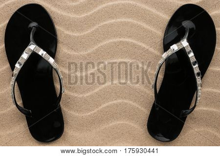Pair of black beach sandals in rhinestones stand on the sand. View from above
