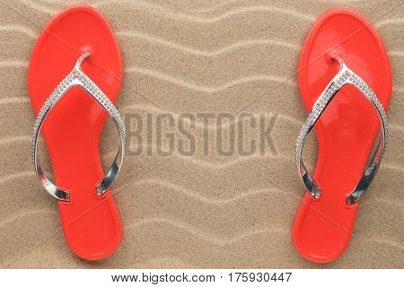 Pair of red beach sandals in rhinestones stand on the sand. View from above