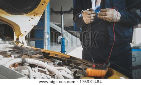 Mechanic electric in car garage workshop works with voltmeter - electrical wiring, close up
