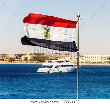 The flag of Egypt evolves against the backdrop of a yacht and the sea.