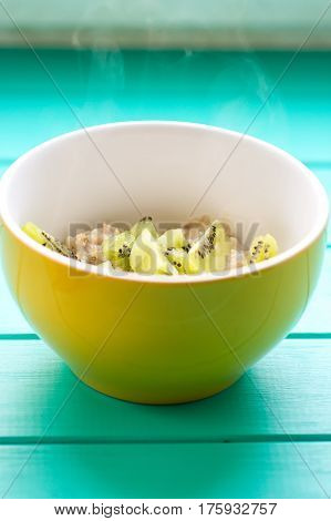 Oatmeal with milk and kiwi in a yellow bowl on a blue wooden table