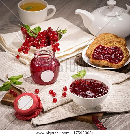 Blackcurrant jam on bread on wooden background