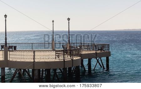 Stone pier on piles with benches lanterns and forged fencing.