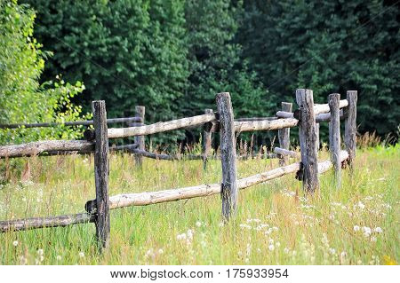 Old wooden rural corral fense in meadow
