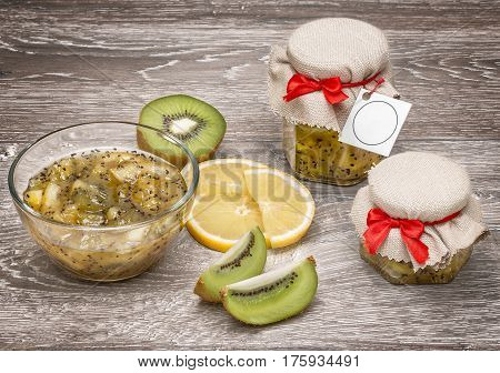 Kiwi fruit, kiwi slices, jam of kiwi on a light wooden background