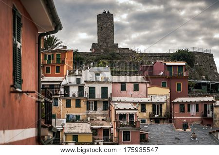 VERNAZZA, ITALY - DECEMBER 2016: Dark town of Vernazza with people on an old tower ruins on a background.