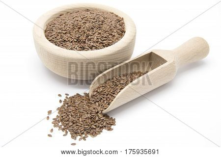 Flaxseeds in wooden scoop and bowl on white isolated background