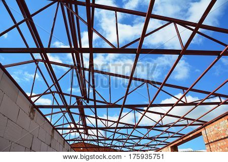 Roofing construction. Steel roof trusses details with clouds sky background. Industrial roofing.