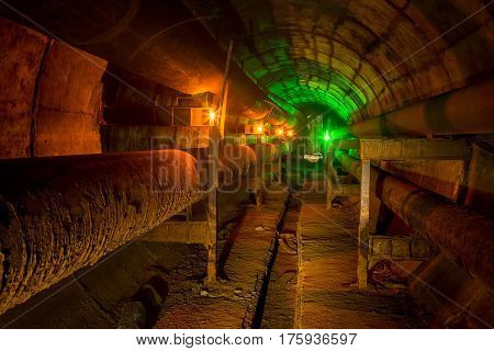 Dirty technological tunnel with rusty pipeline illuminated by candles and green lantern
