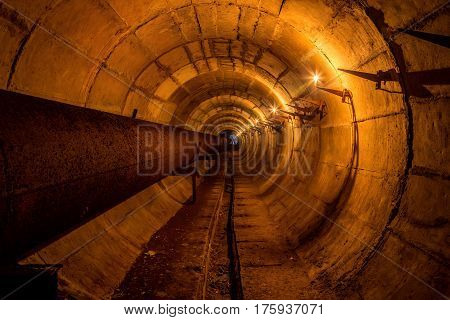 Round underground technical tunnel of heating main with rusty pipeline illuminated by candles