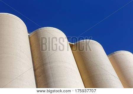 Top of cluster of silos used for storage of grain against a blue sky.