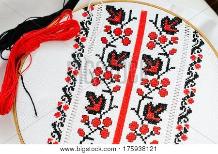 The wooden hoop with the embroidery pattern of red and Black color on canvas. Slavic Embroidery with hemming.