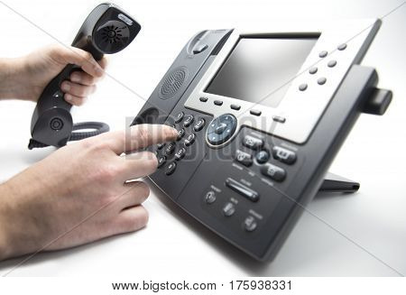 Making a call man is dialing IP telephone keypad