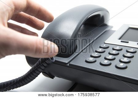 Man is picking up the phone receiver