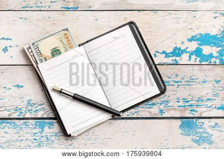 Opened notepad with dollars and pen. Business concept.