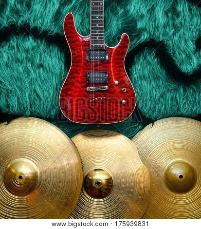 Red Electric guitar with three cymbals on turquoise color faux fur wall. Musical instruments background