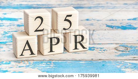 April 25th. Wooden cubes with date of 25 April on old blue wooden background.