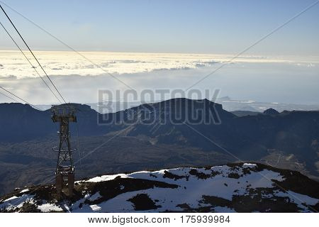 View from top of Teide with the arial railway to the left and mountains and blue sky with clouds in background picture from Tenerife Spain.