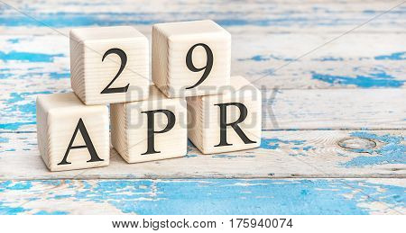 April 29th. Wooden cubes with date of 29 April on old blue wooden background.
