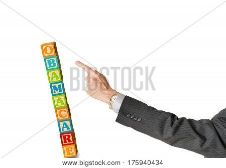 Senior male politician hand pushing over  a stack of childs blocks spelling Obamacare in Congress isolated against white background
