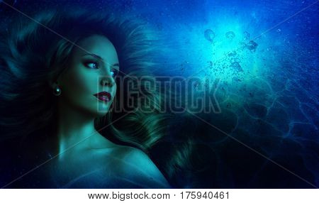 Beautiful girl with long hair in the image of a mermaid under the water