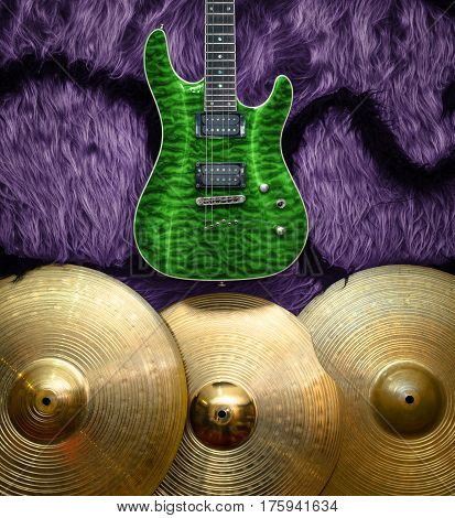 Green electric guitar with three cymbals on faux fur wall. Musical instruments background