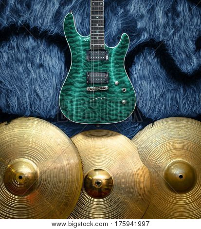 Turquoise electric guitar with three cymbals on blue faux fur wall. Musical instruments background