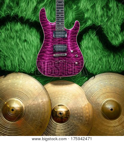 Purple electric guitar with three cymbals on green faux fur wall. Musical instruments background