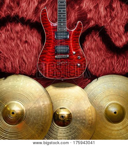 Red Electric guitar with three cymbals on faux fur wall. Musical instruments background