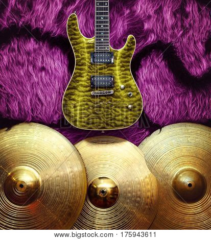 Yellow electric guitar with three cymbals on pink faux fur wall. Musical instruments background