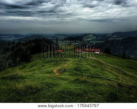 Alpine landscape with green meadows, alpine cottages and mountain peaks,View Idyllic, lake, mountains, green grass, blue sky. Europe