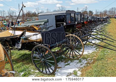 GORDONVILLE PENNSYLVANIA - March 11 2017: Amish carriages for sale at annual spring auction `Amish Mud Sale` to benefit the Fire Company. Sale items include quilts antiques crafts food sporting goods tools farm equipment and horses.