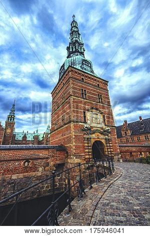 View of the entrance gate to Frederiksborg Palace Denmark in summer cloudy day. Red brick fortress wall and green copper spiels of towers of renaissance castle Frederiksborg.