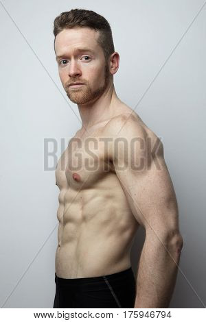 Handsome young man with perfect muscule body posing. White background.