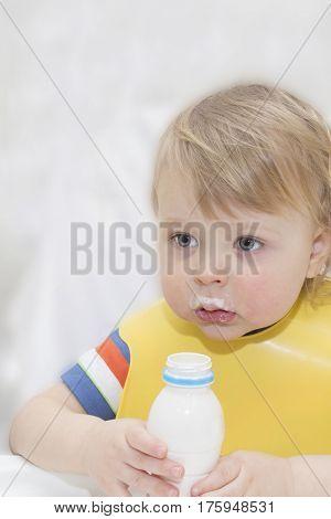 little boy is drinking milk. holding glass of milk.