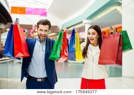 Photo Of Cheerful Stylish Successful Happy Young Lovely Couple Raised  Colored Shopping Bags And Lau