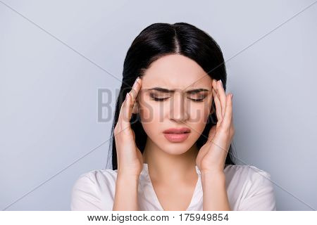 Portrait Of Tired Beautiful Young  Woman With Black Hair  Suffering From Headache On Gray Background