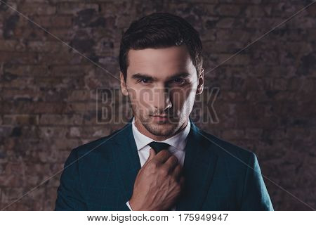 Portrait of confident young businessman in formalwear corecting tie
