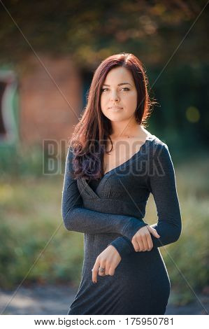 Portrait of beautiful girl with brown hair in grey skinny dress