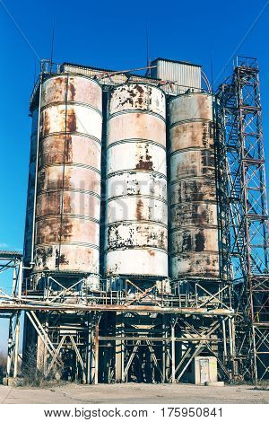 Old, Abandoned Concrete Plant With Iron Rusty Tanks And Metal Structures. Crisis, Collapse Of Econom