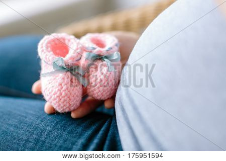 future mother knows a sex of her baby. Pregnant woman holding pink knitted baby bootees at a stomach with selective focus.