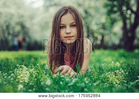 spring closeup outdoor portrait of adorable 11 years old preteen kid girl. Spending spring holidays in beautiful blooming cherry garden