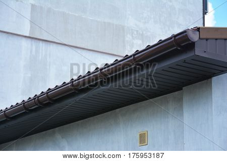 Close up on rain gutter system with roof and soffits